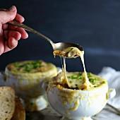 Person isst überbackene Zwiebelsuppe
