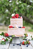 A two-tier cream cake decorated with berries on a table outside