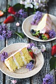 Slices of butter cream cake on plates decorated with flowers and berries