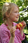 A little girl in a garden holding a fruit skewer