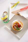 A corn cake with cherry tomatoes, rocket quark and party decorations