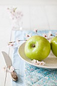 To green apples on a plate with apple blossom