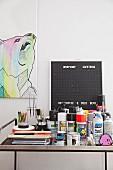 Farbtöpfe, Sprühdosen und Zeichenutensilien auf Ablagetisch aus Metall, dahinter Bild mit Tiermotiv und Tafel
