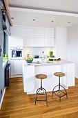 Offene weiße Küche mit Küchentheke und Barhockern im Industriestil