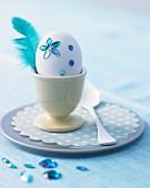 Weisses Hühnerei verziert mit blauen Glitzersteinen & Feder im Eierbecher