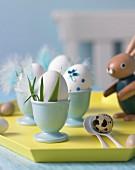 Eier österlich dekoriert in Eierbechern auf Tablett