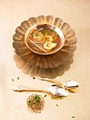 Spicy consommé with spring onions and ravioli