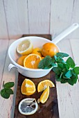 Oranges and lemons in an enamel colander, fresh mint and sliced oranges and lemons on a board