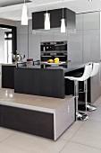 Multifunktionale Küche, Frühstückstheke mit Barhockern, davor angebautes Lowboard, unter Pendelleuchten, in Designerküche