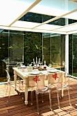Ghost Stühle um gedeckten Tisch auf Holzterrasse eines verglasten Wintergartens, oberhalb abgehängte Decke mit opakem Glas