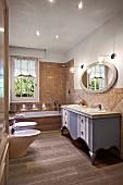 Bad im Landhausstil mit graublau lackiertem Waschtisch, ovalem Wandspiegel, Badewanne, WC und Bidet