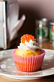 A spicy salmon cupcake topped with cream and caviar