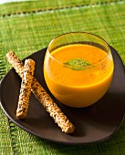 Cold ginger soup with carrots and breadsticks