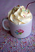 Vanilla milk topped with cream and sugar sprinkles