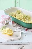 Grüne Kasserolle mit Holunderblüten und Zitrone auf weißem Vintage Schrank