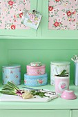 Vintage kitchen dresser with collection of romantic tins and spring onions on chopping board