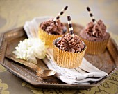 Chocolate cupcakes with striped chocolate wafer rolls
