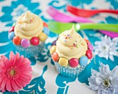 Cupcakes decorated with colourful chocolate beans and sugar sprinkles
