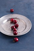 Sweet cherries in a pewter plate