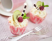 Cupcakes decorated with white chocolate cream, kiwis, raspberries and chocolate cigars