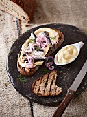 Grilled bread with mayonnaise, sardines in oil and onions