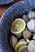 Steamed clams in a white wine broth with garlic and herbs in an enamel pot