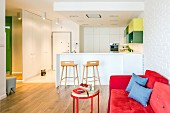 Rotes Sofa und weiße Einbauküche mit Frühstückstheke in offenem Wohnbereich