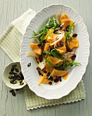 Raw marinated pumpkin salad with rocket, apple, pumpkin seeds and pumpkin seed oil