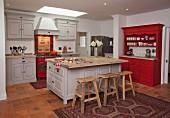 Holz Barhocker vor freistehendem Mittelblock in offener Landhausküche in Hellgrau und Rot, abgehängte Decke mit Einbaustrahlern