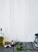 Olivenöl, Knolauch und Basilikum auf gefliester Arbeitsplatte