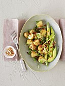 Potato salad with avocado, dried tomatoes and pine nuts
