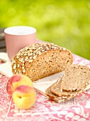 Wholemeal bread with oats and peaches on a garden table