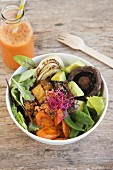 Quinoasalat mit gebratenem Tofu, Gemüse und Pilzen, daneben eine Flasche Karottensaft
