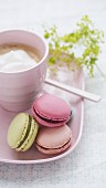 Four colourful macaroons with cafe latte and a sprig of lady's mantle