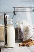 A bottle of milk with vanilla pods, cinnamon sticks, coffee beans, cane sugar and cutters