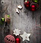 Sterne aus Buchseiten und andere Weihnachtsdeko liegen auf verwittertem Holzuntergrund