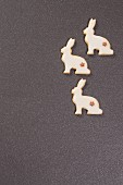 Three festive, rabbit-shaped biscuits on grey surface