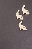 Drei weihnachtliche Hasen-Plätzchen auf grauem Untergrund