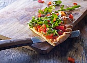 A slice of pizza bread with tomatoes and rocket on a wooden board