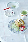 A baked potato with sheep's cheese and green sauce