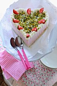 A strawberry heart cake with pistachios
