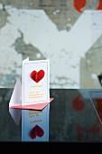 Gutscheinkarte für ein romantisches Abendessen zum Valentinstag, mit aufgenähter Herzmotiv und Suppennudel-Buchstaben