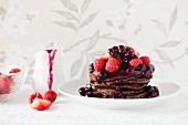 A stack of chocolate pancakes with berries