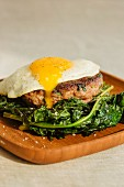 A grilled lamb burger topped with a fried egg and served with sautéed kale