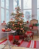 Klassisch geschmückter Weihnachtsbaum in Rot-Weiß mit Lebkuchen- und Stoffanhängern und Kerzen in einem Wintergarten