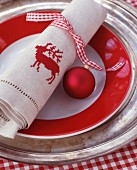 Red and white gingham ribbon, bauble and linen napkin embroidered with stag motif