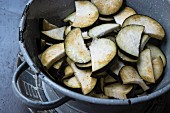 Aubergines sprinkled with fleur de sel in a colander
