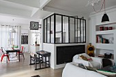 Teilverglaster Küchenbereich in offenem Wohnraum mit Esstisch und Couch