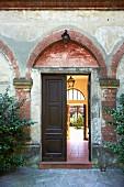 Halboffene Flügeltür mit Blick in den Innenhof eines italienischen Herrenhauses mit abgeblätterter Fassade
