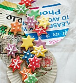 Colourful Christmas star biscuits on paper plates